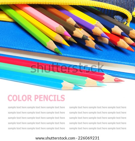Colour pencils and a blue note book isolated on white background