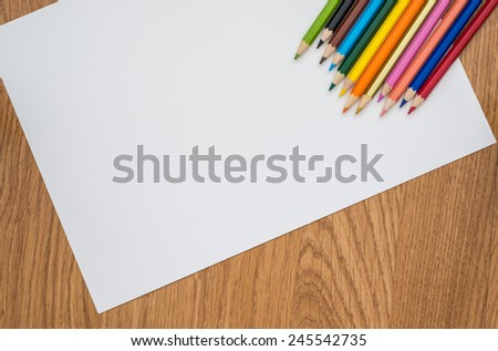 Colour pencils isolated on white paper and wooden background close up - stock photo