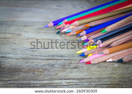 Colour pencils on wood background close up - stock photo
