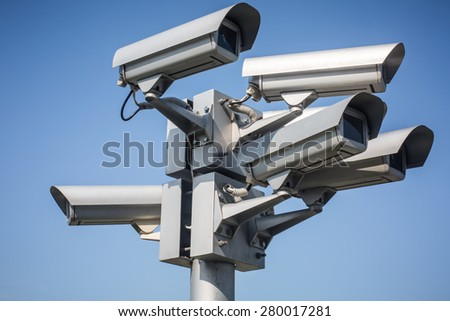 Colour picture of surveillance cameras on blue background - stock photo