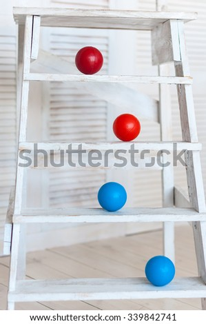 Colour plastic balls on wooden stairs for background. - stock photo