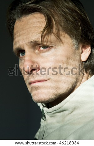 colour portrait photo of a pensive and serious looking man in his forties with blue eyes and brown hair. - stock photo