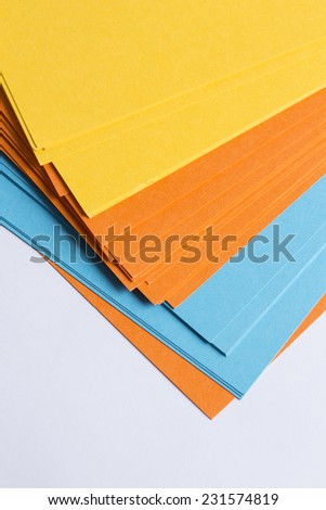 coloured card board sheets in orange, yellow and blue on a white table  - stock photo