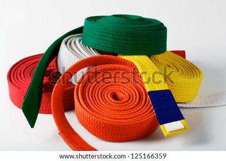 Coloured karate belts on white - stock photo