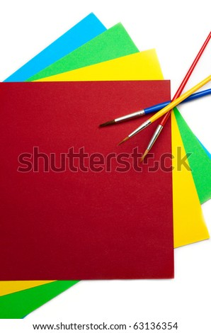 Coloured paper and brushes isolated on white