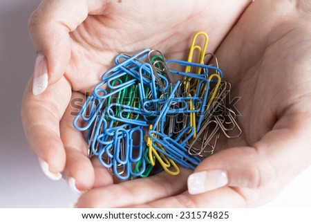 coloured paperclips in a female hands on white table - stock photo