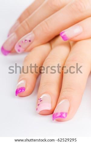 coloured pink female fingernails on white ground - stock photo