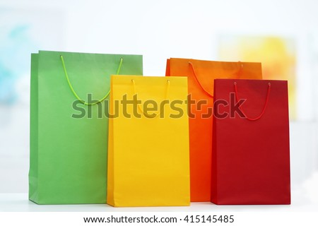 Coloured shopping bags on bright background