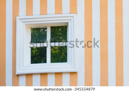 Coloured wall with one white window.