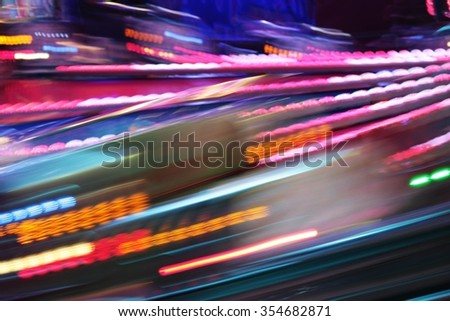 Colourful amusement funfair park ride with night lights blur - stock photo