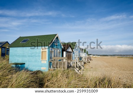 Colourful beach huts on Mudeford Spit at Hengsibury Head near Christchurch in Dorset - stock photo