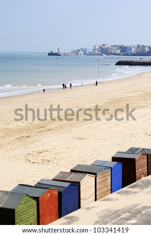 Colourful beach huts overlooking Margate Harbour - stock photo