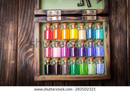 colourful beads in mini retro glass bottles. Handmade set in box - stock photo