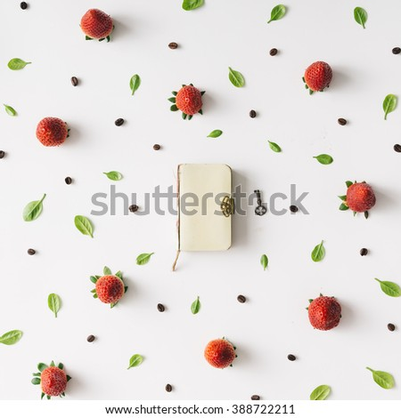 Colourful bright pattern made of strawberries, coffee beans and leaves with vintage notebook. - stock photo
