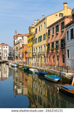 Colourful buildings in Venice during the day. Reflections can be seen in the water along with boats - stock photo