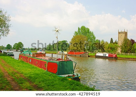 Colourful canal barge moored at Frampton on Severn with a distant view of St Mary the Virgin Church on the Gloucester to Sharpness canal in soft late afternoon sunlight, Gloucestershire, U K - stock photo