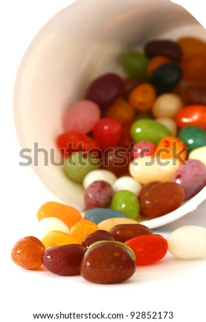 Colourful candies in a pot and scattered on white background - stock photo