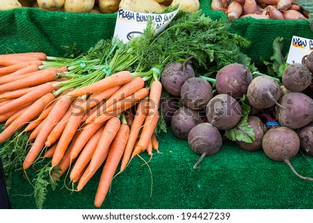 Colourful carrots and beetroot, in a display on a market stall.