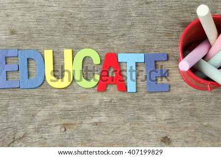 Colourful chalk and word EDUCATE on wooden table. Concept of teaching and education. - stock photo