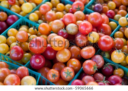 Colourful cherry tomaties in small green baskets - stock photo