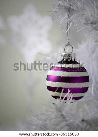 Colourful christmas baubles hanging from white christmas tree - stock photo