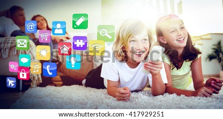 Colourful computer applications against siblings lying on the floor watching tv - stock photo
