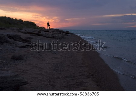 Colourful decline on lake Issyk-Kul (Kirghizia). The man the photographer admires the leaving sun. - stock photo