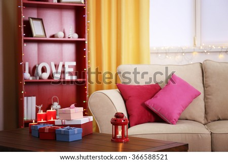 Colourful decorated interior. Comfortable living room, table with gift boxes and candles on it is close up - stock photo