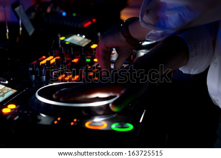 Colourful DJ music deck at night with all the controls illuminated and the hand of the disc jockey suspended above the vinyl record on the turntable to mix and scratch the audio for the disco - stock photo