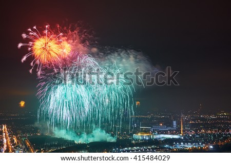 Colourful firework  in night sky over city. - stock photo