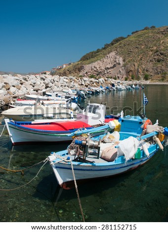 Colourful fishing boats moored in a small Greek harbor - stock photo