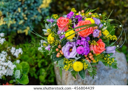 Colourful flower arrangement in a purple pot. Peach rose, purple, lilac eustoma (lisianthus) flowers, yellow chrysanthemum, berries, garden flowers. Outdoor decor. Birthday, greeting card. - stock photo