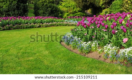 Colourful Flowerbed and Grass Lawn in an Attractive Garden - stock photo