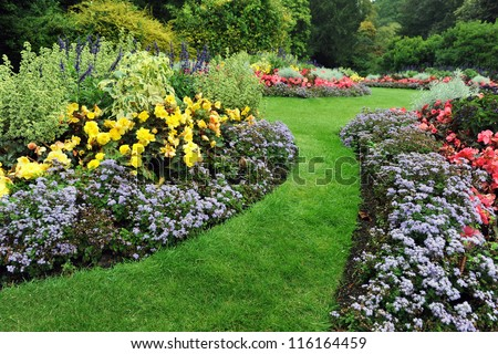 Colourful Flowerbeds and Winding Grass Pathway in an Attractive English Formal Garden - stock photo