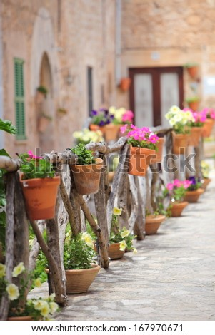colourful flowers on a rustic wooden fence outside Row of flowerpots filled with colourful flowers on a rustic wooden fence outside an old stone building lining a street - stock photo