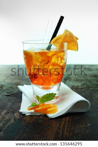 Colourful glass of rum and orange cocktail garnished with fresh fruit, rind and mint leaves standing on an old wooden bar counter - stock photo