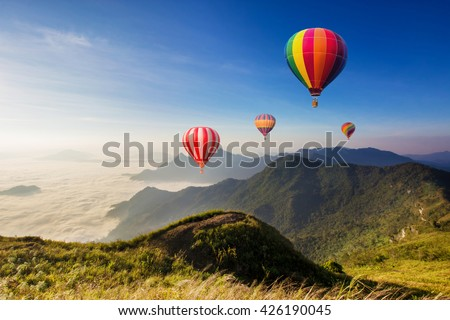 Colourful hot-air balloons flying over the mountain at Phucheefa,Chiangrai province ,North of Thailand. - stock photo
