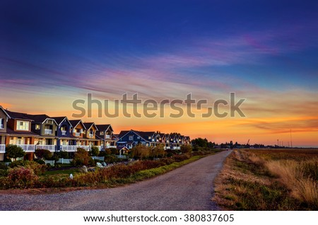 Colourful, identical houses by the river, during sunset  - stock photo