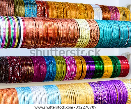 Colourful Indian wrist bracelets stacked in piles on display at a shop in Little India in Singapore. Colorful urban concept - stock photo