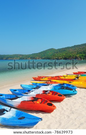 Colourful kayaks on the beach. - stock photo