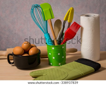 colourful kitchen utensils in green bucket and eggs - stock photo