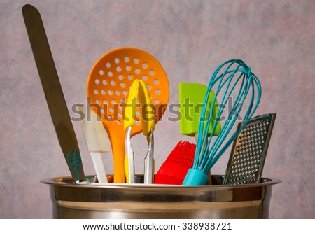 colourful kitchen utensils in metal bowl - stock photo
