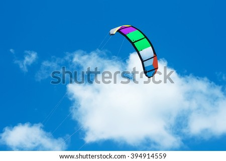 colourful kite in cloudy sky - stock photo