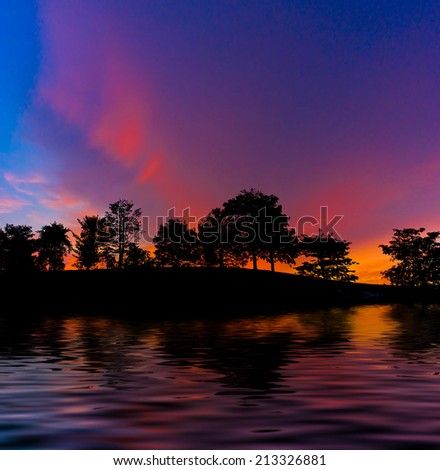 colourful landscape with silhouette trees during sunset. digital compositing with colour tone, water reflection and ripple effects. - stock photo