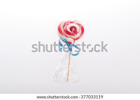 Colourful lollipop in the shape of a heart isolated on white background, a festive treat, a gift favorite, original declaration of love, the abuse of sweets faces caries - stock photo