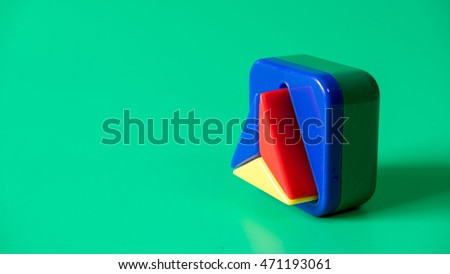 Colourful mix of round, triangle and square shape. Isolated on green background. Slightly de-focused and close-up shot. Copy space.