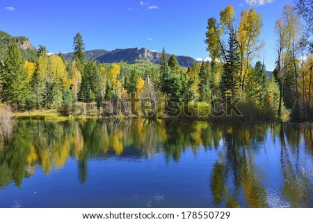 colourful mountains of Colorado reflecting in a lake during foliage season - stock photo