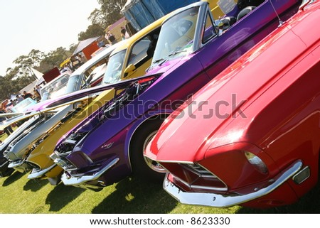 Colourful muscle cars with bonnets open in a row - stock photo