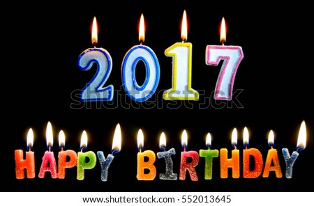Colourful of 2017 happy birthday candle with flame lighting on the black screen