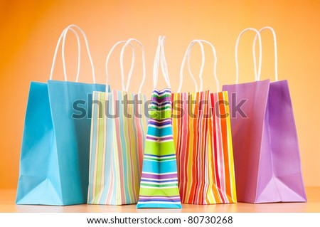 Colourful paper shopping bags against gradient background - stock photo